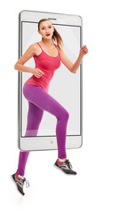 Portrait of young sporty woman jogging on white background, concept virtual reality of the smartphone. going out of the device