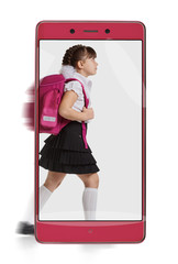 Side view photo of little girl with schoolbag going to school. conceptual image with a smartphone, demonstration of device capabilities