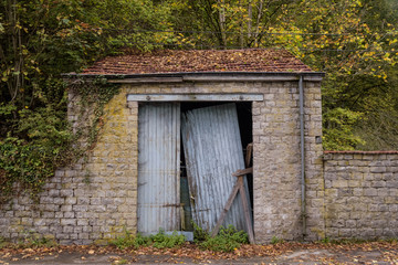 Old left behind garage in autumn scenery