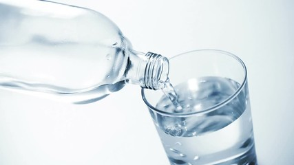Fototapete - Looping cinemagraph, pouring clear water into glass on blue background
