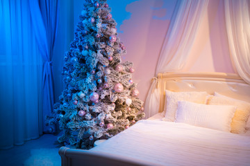 Christmas tree in the bedroom. Feast of the Nativit. Xmas decorations.