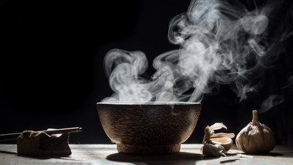 Bowl of hot soup with chopstick,spices on black background