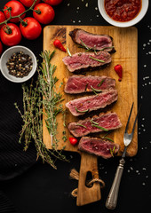 Slices of beef steak on meat fork on wooden cutting board.