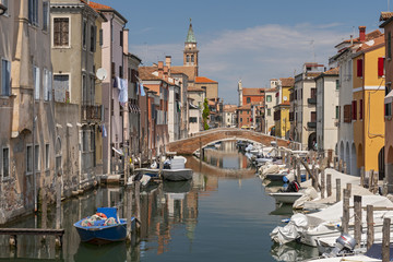 View of the city of Chioggia with wooden boats and bridge over canal, little Venice Italy.