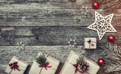Christmas greeting card of horizontal shape, on old wooden background. Gifts and handmade toys. Space for text. Top view. Effects