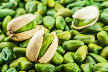 Green pistachio nuts with shell over lot of pistachios.