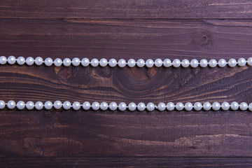 Wooden background and two pearls, place for text.