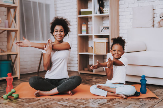Mother and young daughter doing yoga together at home