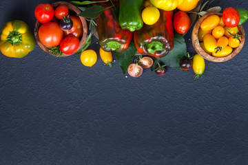 Assorted tomatoes and vegetables on dark background. Photo for your design.