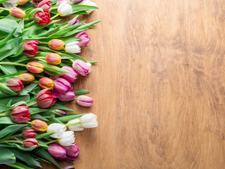 Colorful  bouquet of tulips on wooden background.