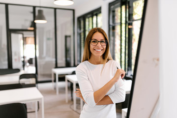 Portrait of a smiling young woman in modern classroom or conference room.