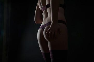junge normale schöne frau stehend liegend sexy in dunklen dessous unterwäsche po rücken beine hintern