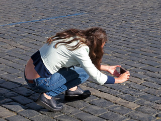 Girl in blue jeans with low waist taking pics with a smartphone on the street. Woman tourist, female denim fashion, mobile photography