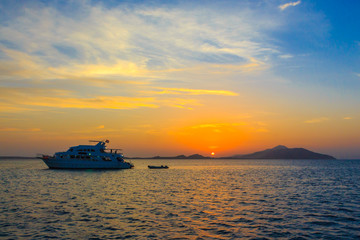 Yacht in the rays of the setting sun against the island of Tirana. Red sea. Egypt.