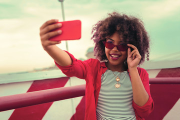 Wearing red glasses. Beautiful fashionable woman smiling and feeling confident while wearing lovely red glasses for the selfie