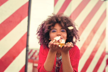 Blowing glitter. Cute young curly woman smiling while blowing nice glitter from her hands