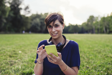 Young adult woman using a mobile phone at the public park in summer