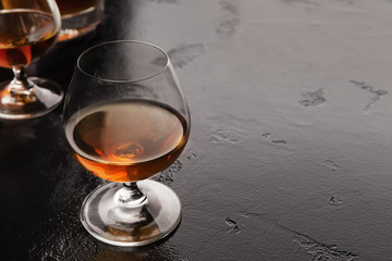 Cognac portions in glass on black background