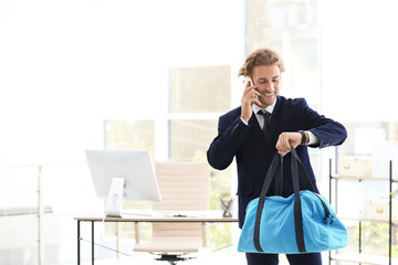 Young handsome businessman holding fitness bag in office. Space for text