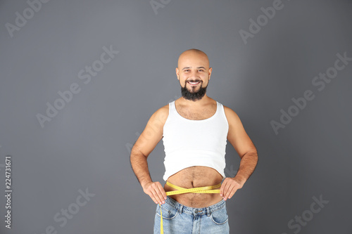 Overweight Man With Measuring Tape On Gray Background Stock
