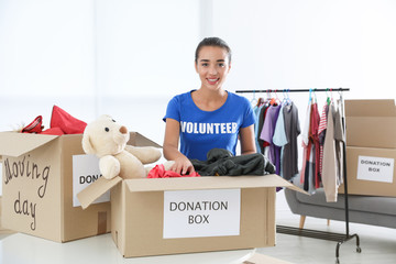Female volunteer collecting donations at table indoors