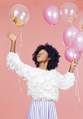 Smiling woman catching pink and gold confetti balloons, isolated on pink studio background