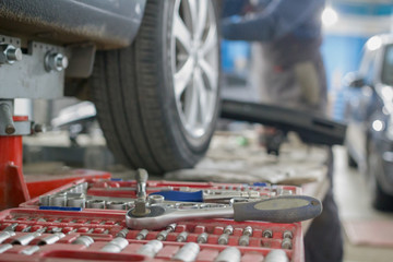 Mechanic tools lie next to the car's wheel on repair