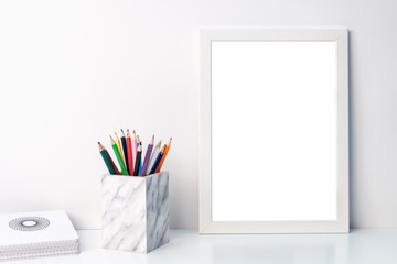 White mockup frame, notebooks and colored pencils in a marble container on a shelf