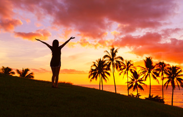 Happy female with arms up enjoying a beautiful tropical sunset.