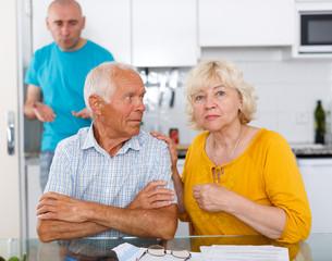 Upset mature parents discussing after quarrel with son