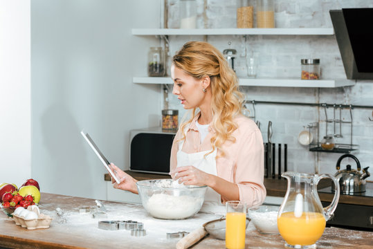 beautiful young woman making dough and using tablet at kitchen