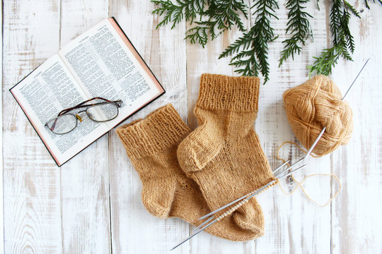 Knit a sock, brown, read the Bible, glasses. Rest, autumn mood. The concept of retirement age and quiet old age.