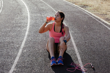 Woman drinking water on racetrack