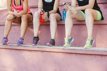 Crop women sitting on tribune with energy drink