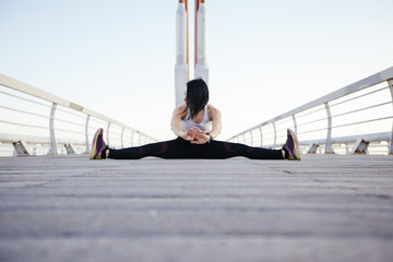 Woman stretching on paved footbridge