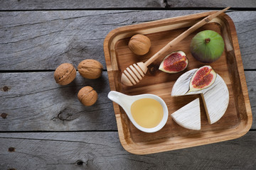 Wooden serving tray with camembert, fig fruits, honey and walnuts. Top view on a grey rustic wooden background