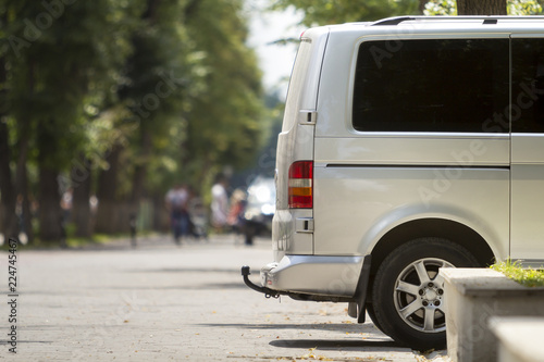 cf3ee60c21 Side view detail of white passenger medium size luxury minibus van parked  on summer city street pavement with blurred silhouettes of pedestrians on  green ...