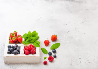 Fresh raw organic berries in white vintage wooden box on kitchen table background. Space for text. Top view. Strawberry, Raspberry, Blueberry and Mint leaf