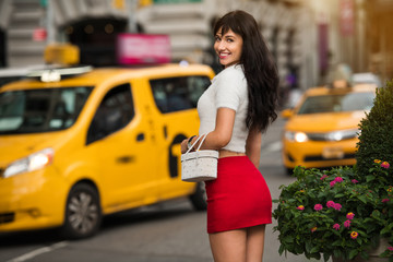 Beautiful elegant smiling woman walking to yellow taxi on city street of New York