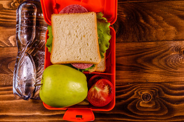Bottle of water, green apple and lunch box with sandwich, cucumbers and tomatoes on wooden table. Top view