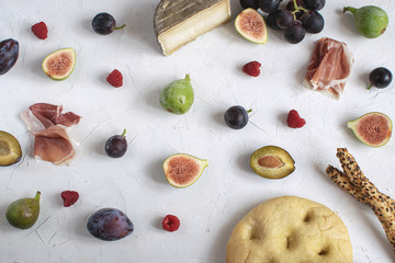 Flat kay italian wine appetizer Fig Grape Plum Cheese Focaccia Grissini Raspberry White background Copy space