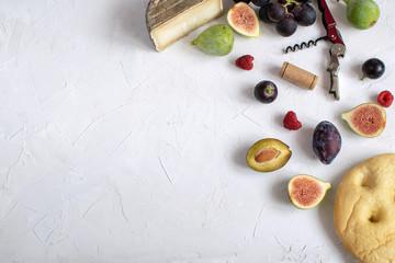 Flat lay italian aperitivo Wine appetizer Fig Prosciutto Grape Plum Cheese Focaccia Grissini Raspberry Corkscrew White background Copy space Vibrant colors