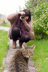 young brunette woman with camera, woman taking photo of grey striped cat outside in the park