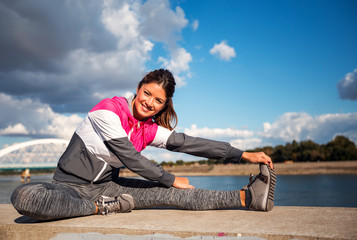 Active woman doing legs stretching before workout in an urban area