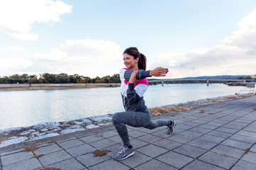 Athlete woman stretching arms in urban area