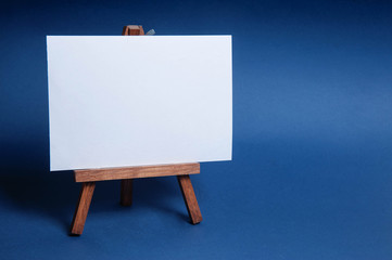 The easel is empty for drawing isolated on blue background. Object