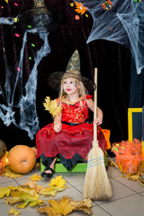 A child, a little girl in the shape of a witch on a broomstick, poses against the backdrop of scenery of cobwebs, pumpkins and autumn leaves on a Halloween holiday.