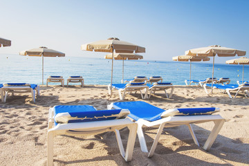Loungers on a tropical beach. Sun beds and umbrellas on a sandy beach. Summer vacation at the sea