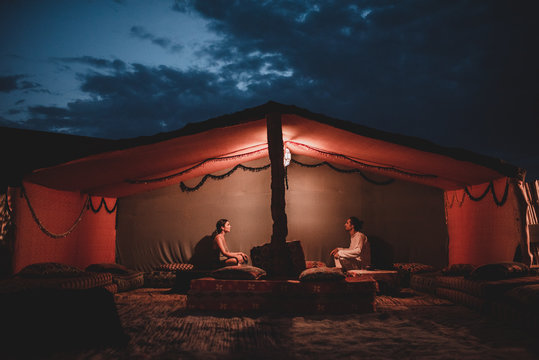 Man and woman sitting in tent