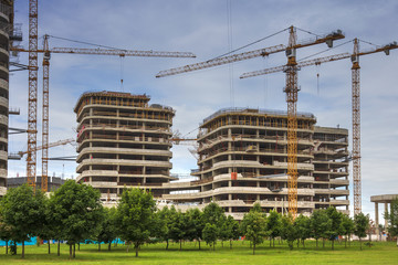 Construction site. Large tower cranes build a new house. Building concept.